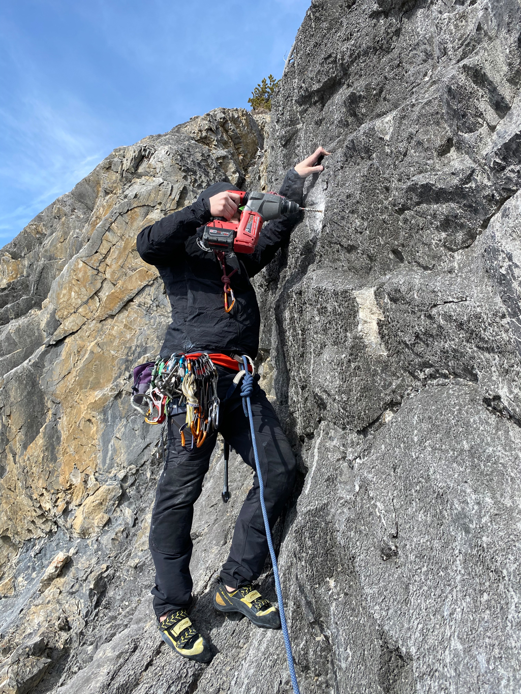 Andrew Abel bolting the little ledge off the third belay on Dumbo